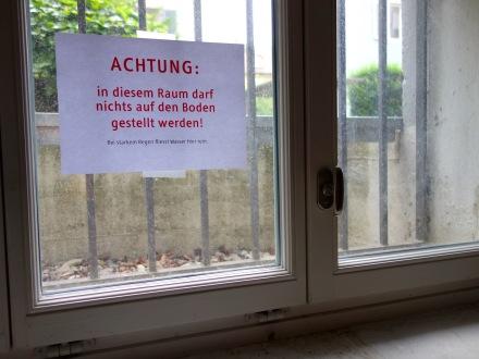 »ACHTUNG: in diesem Raum darf nichts auf den Boden gestellt werden! Bei starkem Regen fließt Wasser hier rein.« Folgendes Bild: Der Boden.